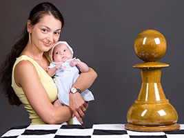Francesca, the daughter of Granmaster Alexandra Kosteniuk poses with chess pieces